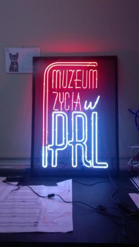 muzeum życia w PRL - neon podświetlony po obrysie liter